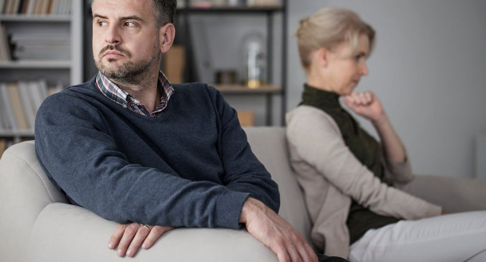 Man turned away from wife sitting next to him on couch after arguing during therapy session