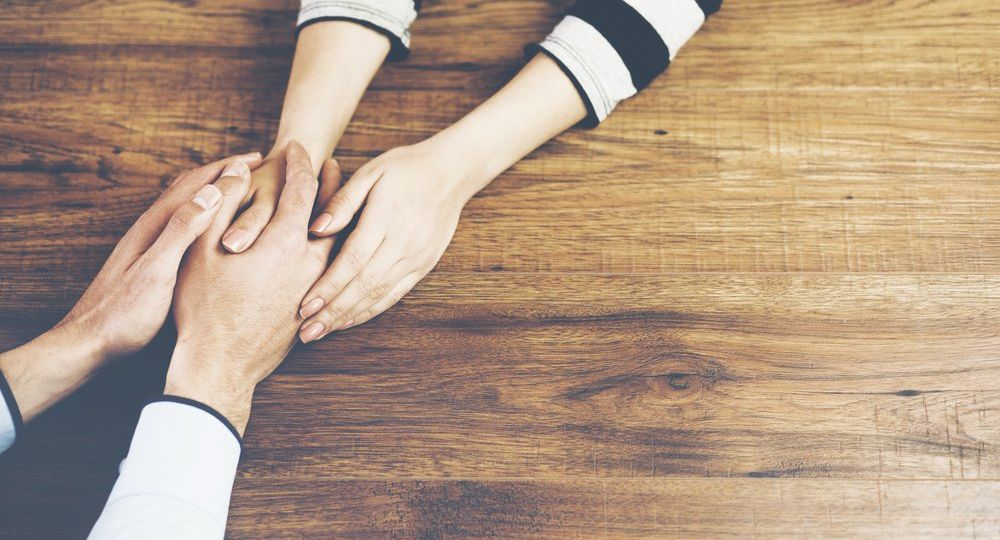 Holding hands across a brown wooden table
